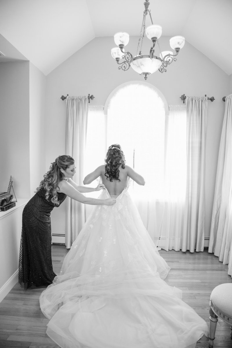 black and white  maid of honor helps bride into wedding gown