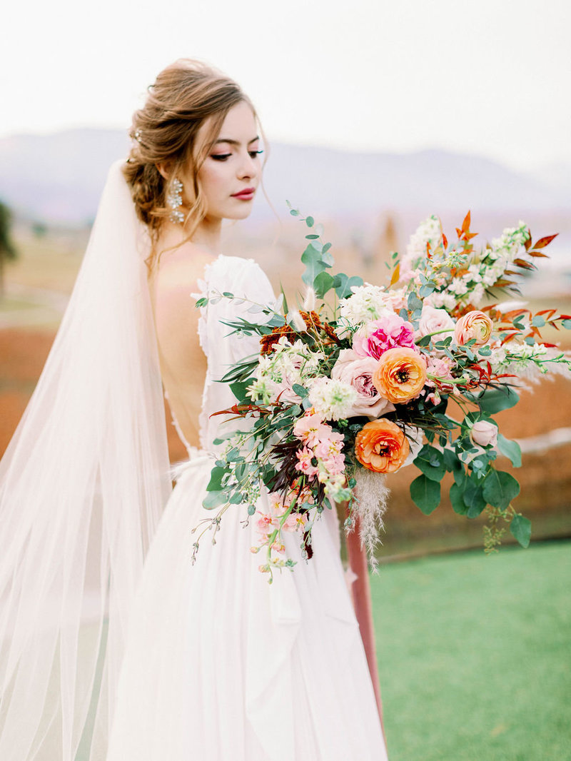 Bride in deep v back wedding dress holding wedding bouquet filled with colorful garden roses for fall Lake Chelan wedding