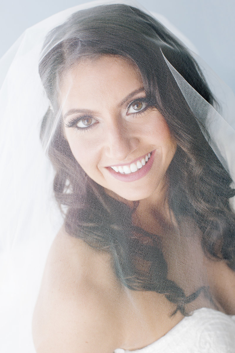 bride smiles under veil into camera