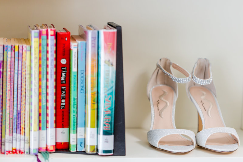 Wedding shoes on a Library bookshelf with a stack of books