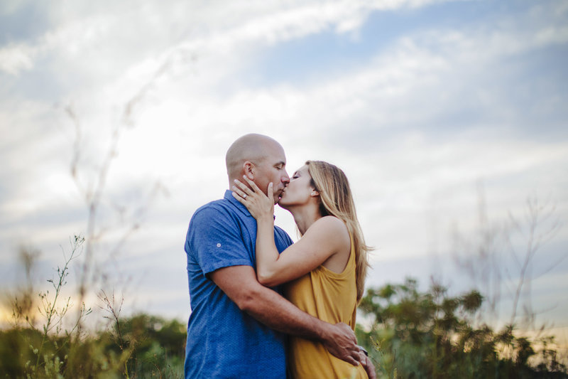 vibrant couple kissing in a lush field