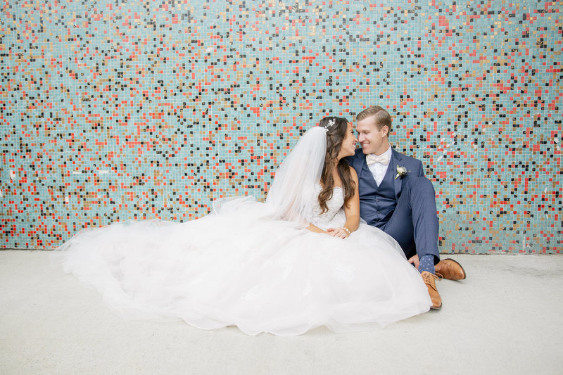 relaxed bride and groom in front of colorful wall in asbury park
