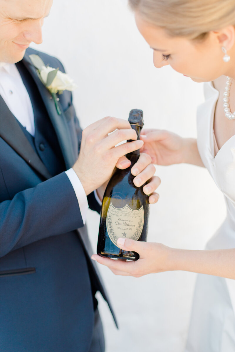 couple opening up bottle of dom perignon champagne ta Inn at Perry Cabin wedding in St Michaels Maryland by Costola Photography