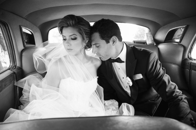 black and white intimate moment with bride and groom in rolls-royce car
