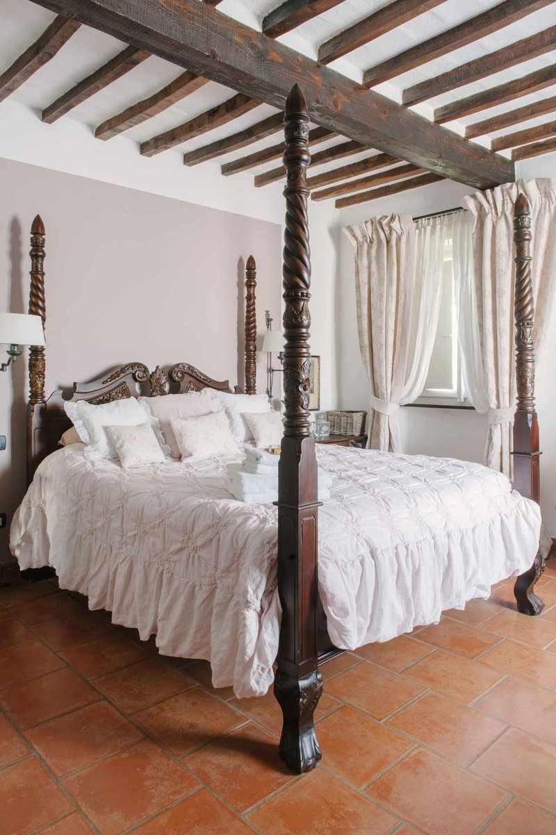 Bedroom in B&B Casa Capanni decorated with 'Per Lei' chalk paint, Arte Pura linens, and curtains by Peony & Sage, realised by Arte di Vita Interiors.