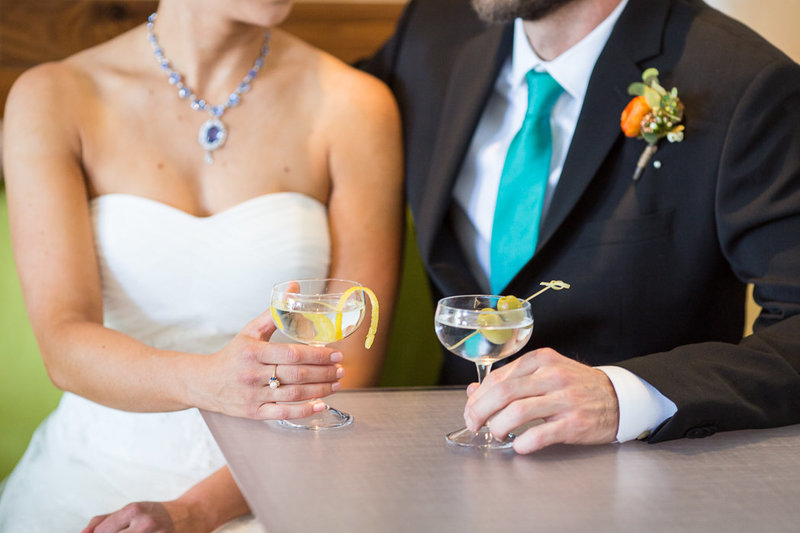 A close up photograph of two martinis, one garnished with a lemon peel, the other with green olives, held by a bride and groom sitting on a lime green upholstered bench in a modern bar in Boise, Idaho.
