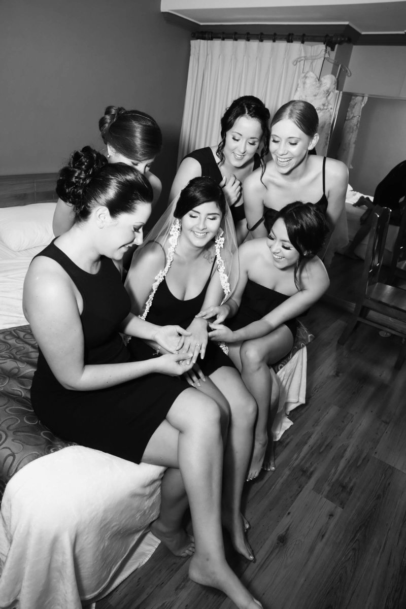 B+W image of bride showing off her engagement ring to her bridesmaids while they get ready for the big event. Photo by Ross Photography, Trinidad, W.I..