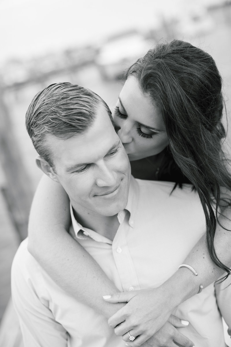 black and white of woman kissing the side of mans face