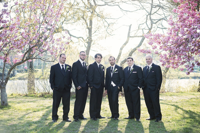 groomsmen standing in front of cherry blossoms