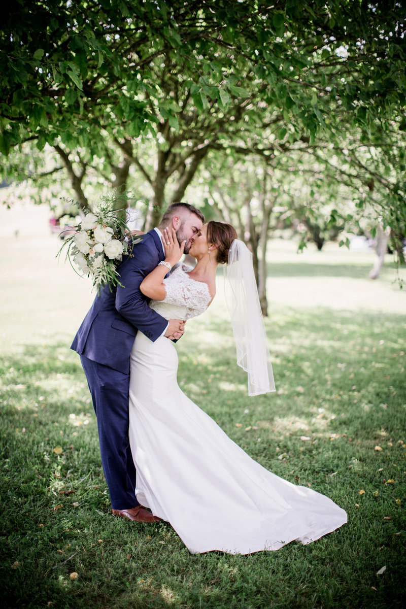Groom kissing his bride by Knoxville Wedding Photographer, Amanda May Photos.
