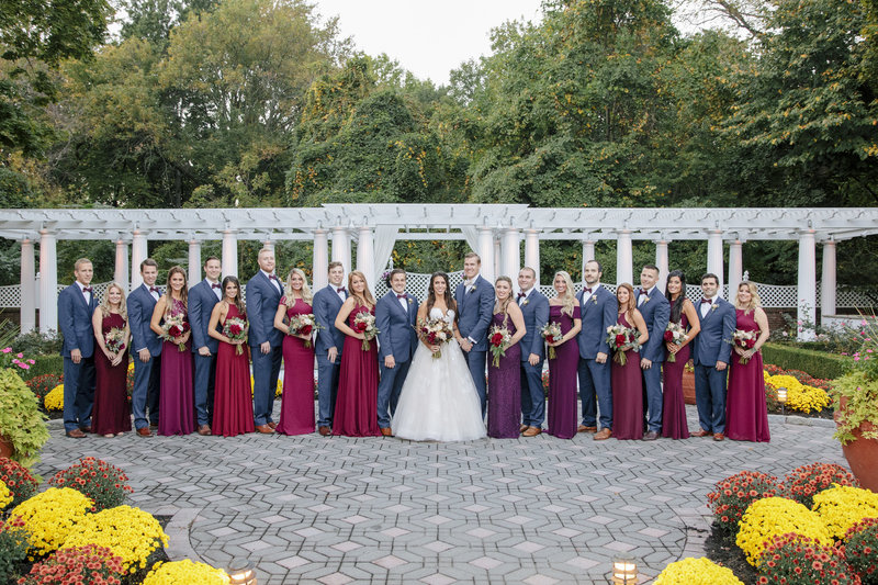 bridal party formal photo in front of gardens and pillars