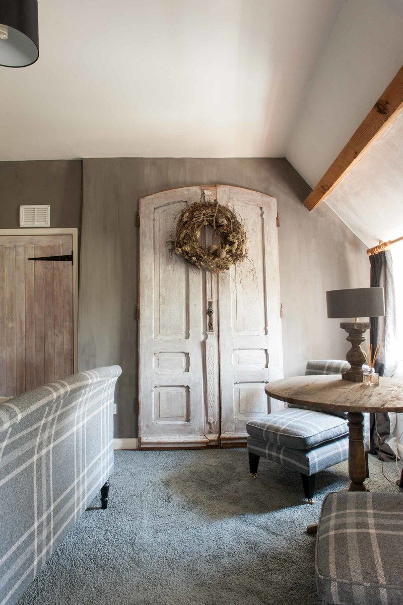 Set of old French doors in bedroom at English cottage, realised by Arte di Vita Interiors.