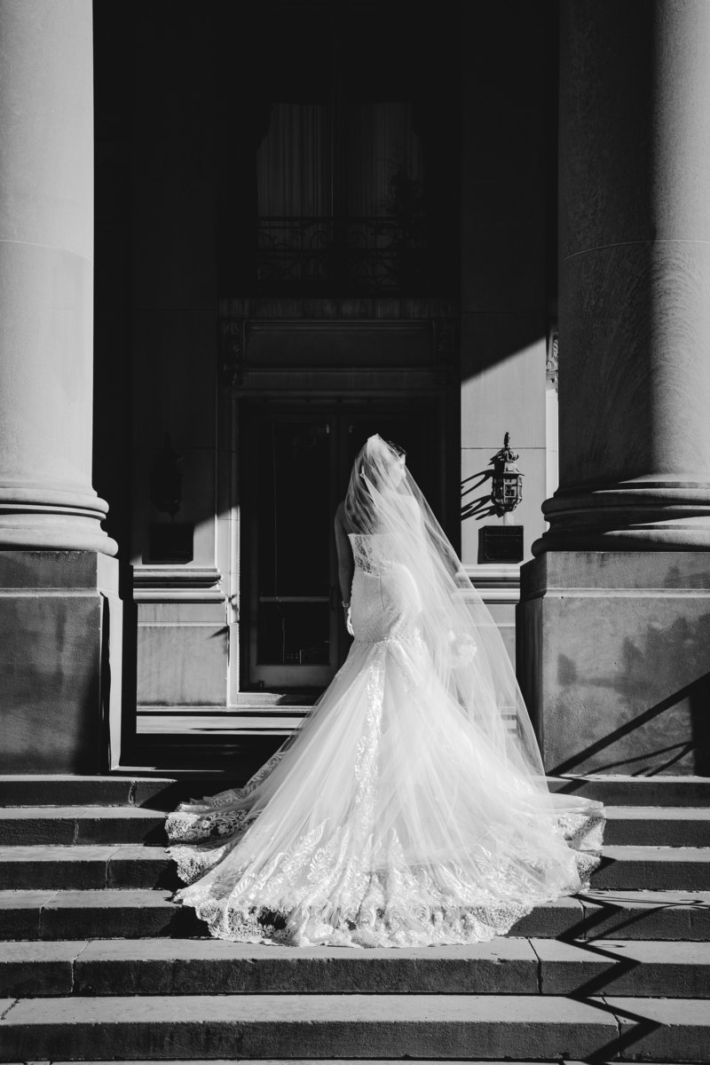 black and white bride walks up grand stairs at monmouth university