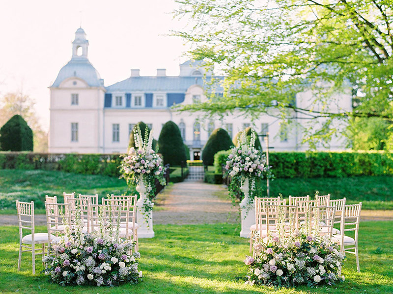 Outdoor wedding ceremony with dusty purple flowers at kronovalls vinslott