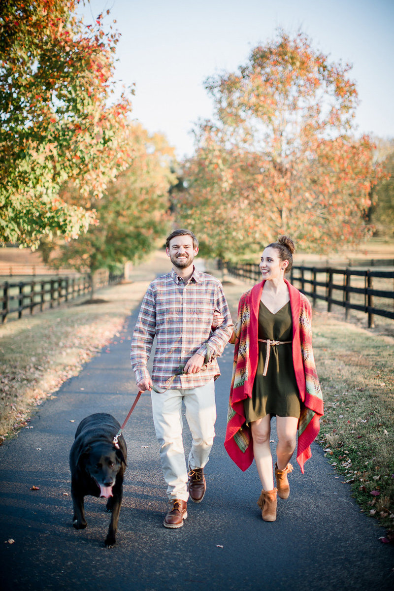Walking their dog with fall colored trees behind them on private property by Knoxville Wedding Photographer, Amanda May Photos.