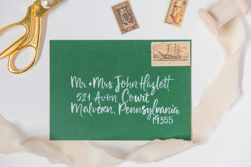 Watercolor calligraphy with white ink on a green envelope  by Katy of Lewes Lettering Co.