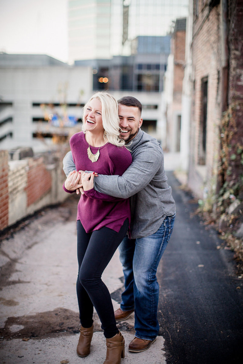 He sneaks up behind her and makes her laugh in downtown Knoxville alley by Knoxville Wedding Photographer, Amanda May Photos.