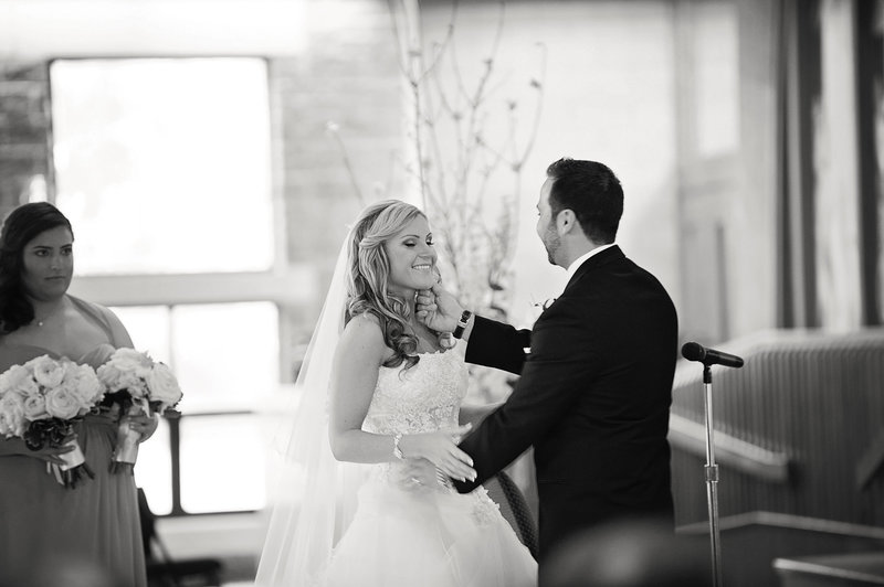 black and white photo of groom touching brides face at wedding ceremony