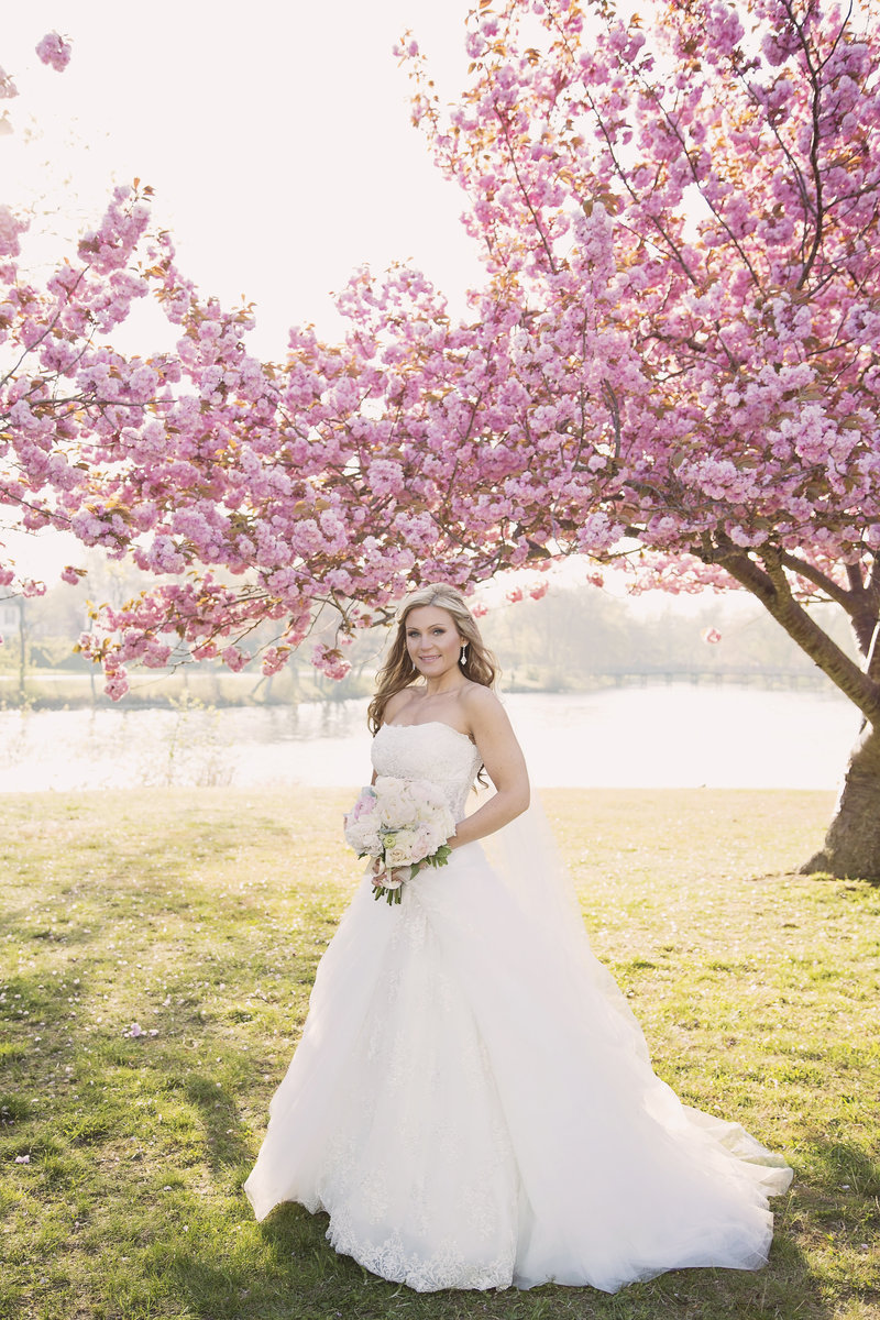 full length bride standing in front of cherry blossom trees