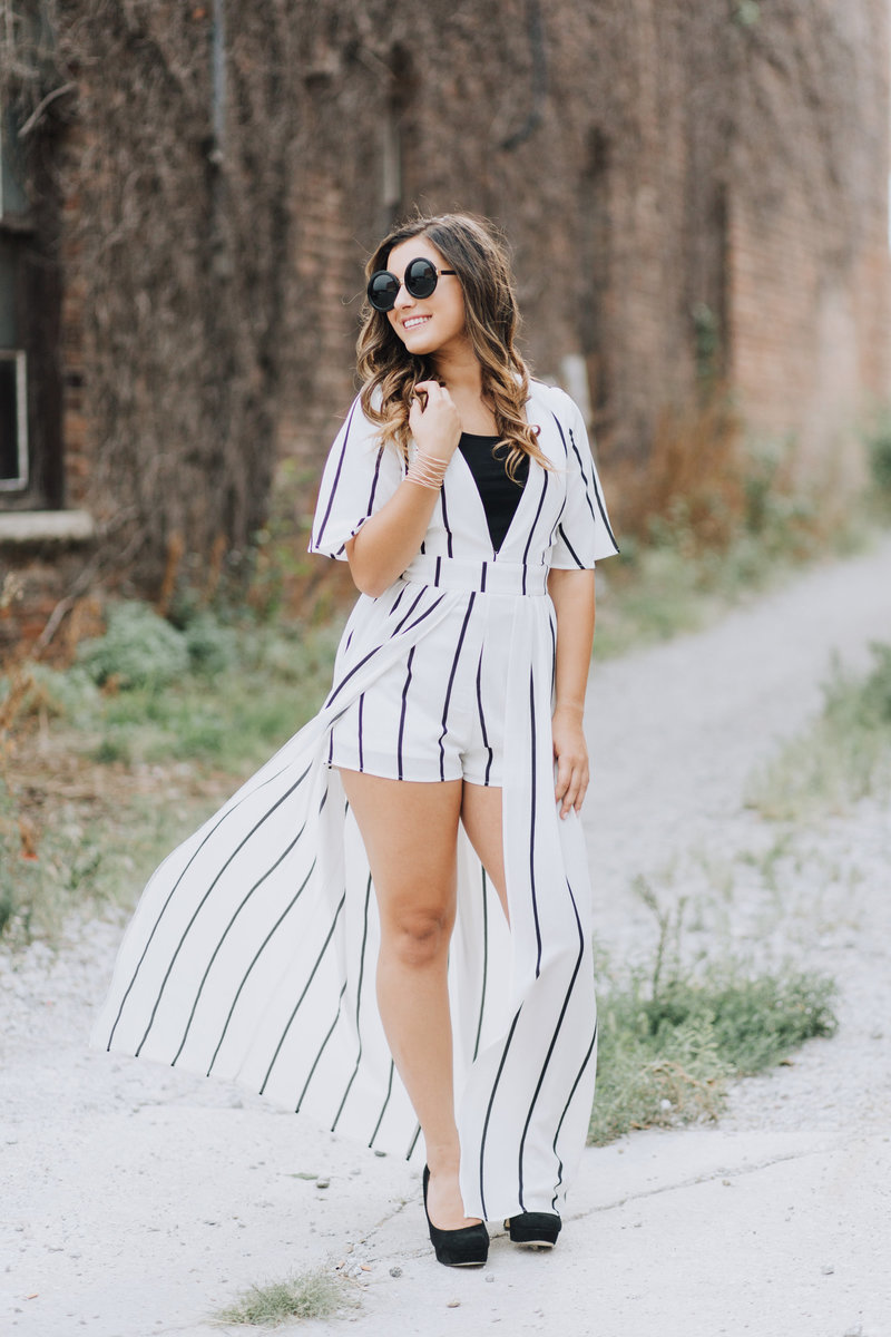striped dress shorts cape black sunglasses standing in alleyway