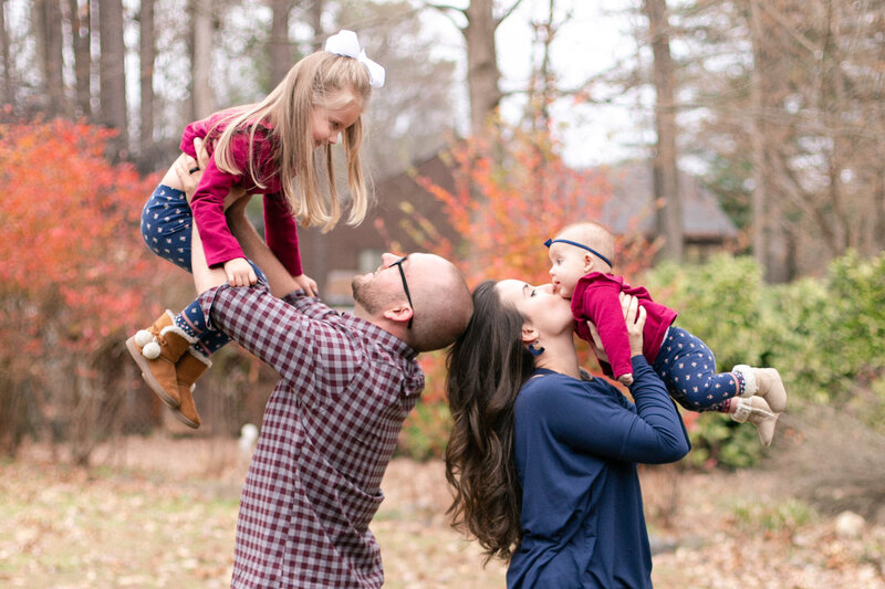 mom and dad hold daughters in the air in kennesaw