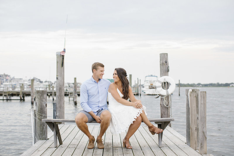 couple looking at each other while sitting on bench on a dock