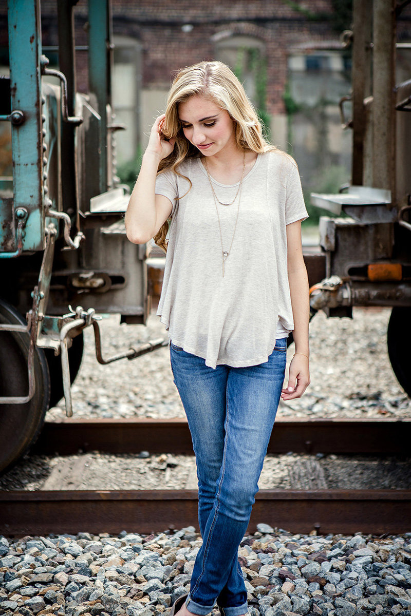 Senior girl standing in front of train looking down with her legs crossed by Knoxville Wedding Photographer, Amanda May Photos.