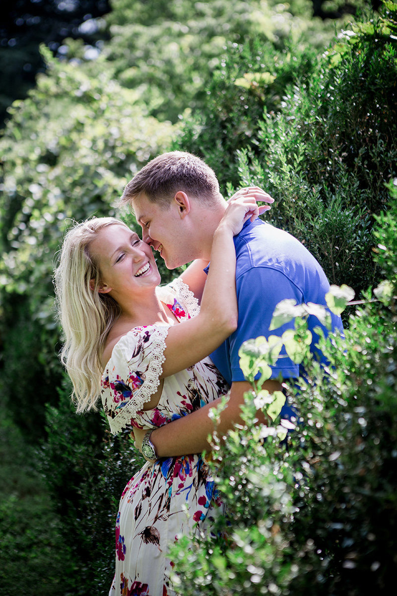 Arms around his neck in the bushes at Knoxville Botanical Gardens Wedding Venue, by Knoxville Wedding Photographer, Amanda  May PHotos