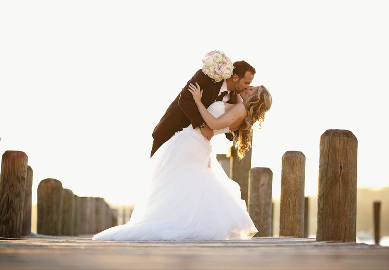 groom dips and kisses bride on dock