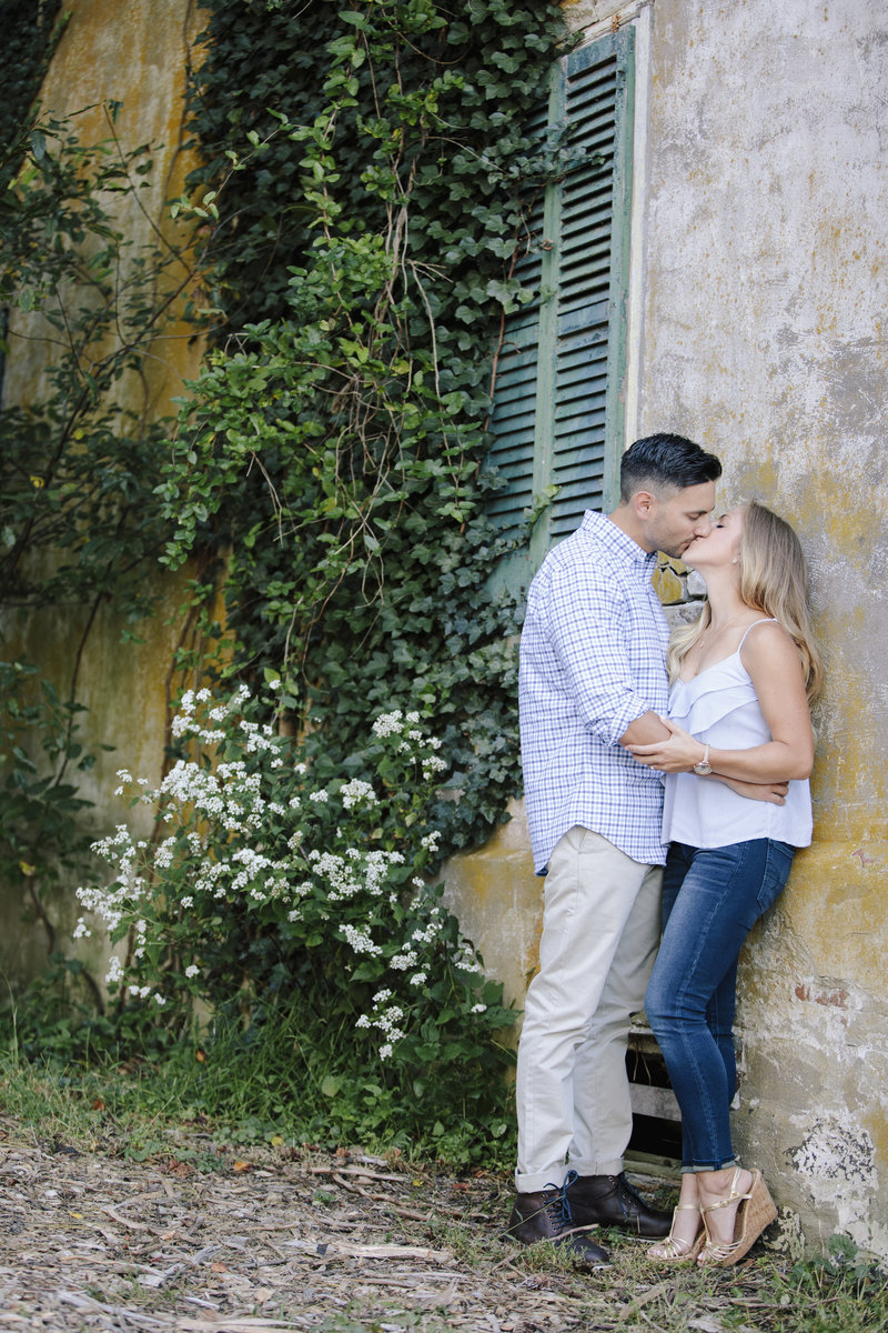 couple kissing in front of large old stone building