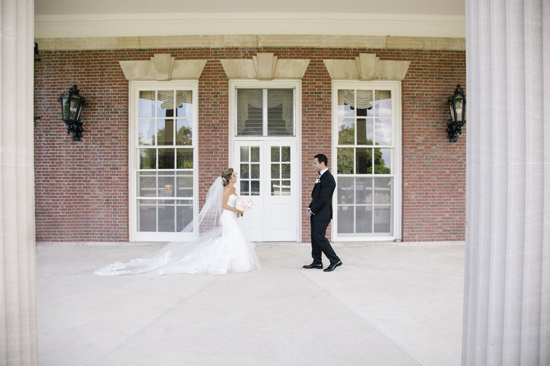 first look with bride and groom in front of brick building