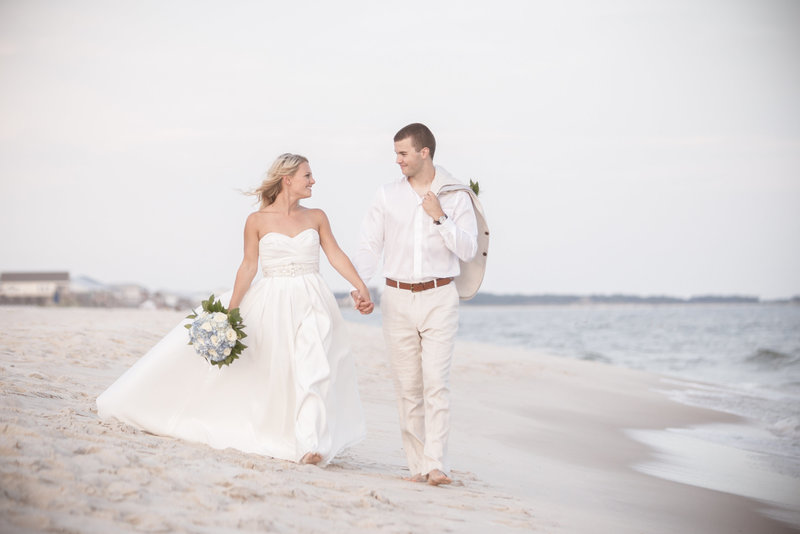 Leah and Brock Little strolling the beach on their wedding day in Dauphin Island, Alabama.