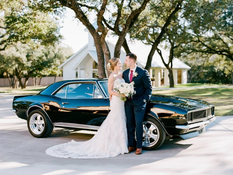 bride and groom with getaway old camaro
