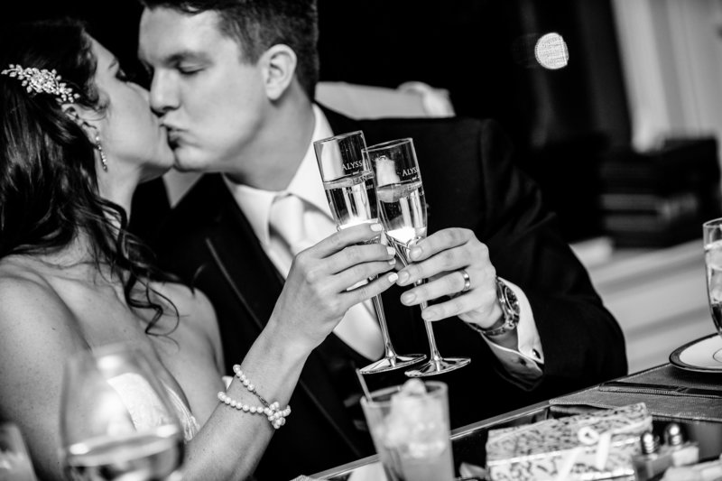 black and white groom and bride kissing and cheers with champagne