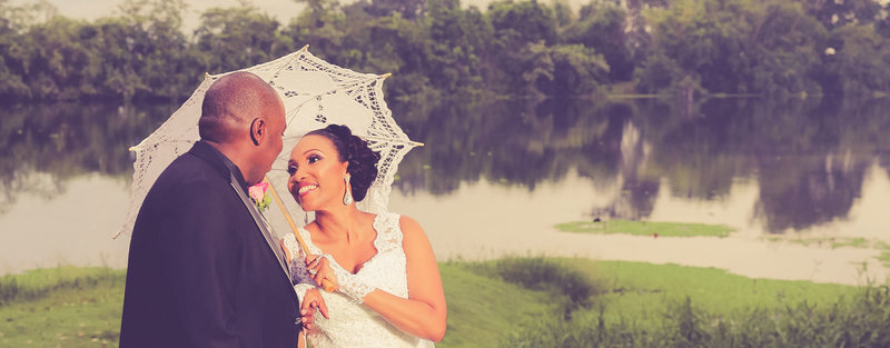 Bride holds vintage, white, lace umbrella as she smiles happily at groom in an outdoor shot. Photo by Ross Photography, Trinidad W.I..