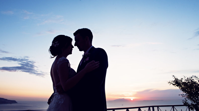 Bride and Groom on the balcony at sunset at the Relais Blu overlooking Capri