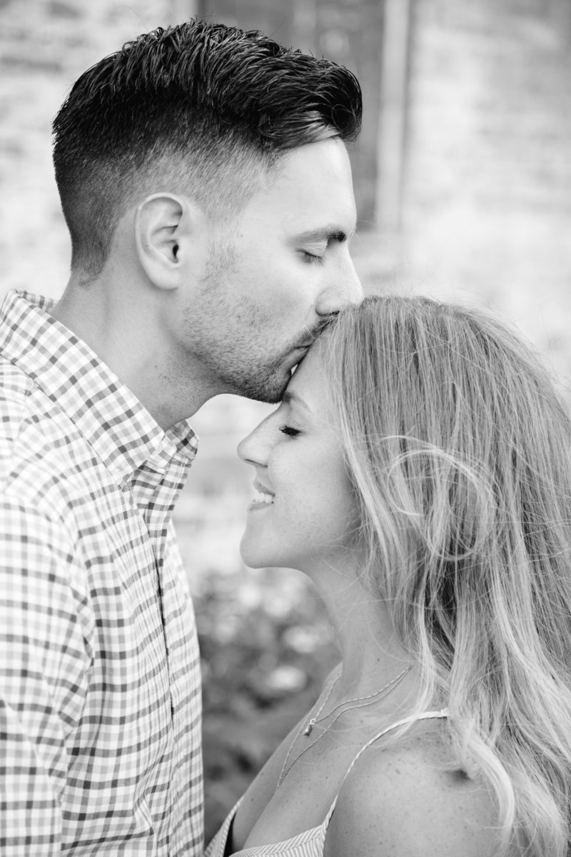 black and white of man kissing womans forehead