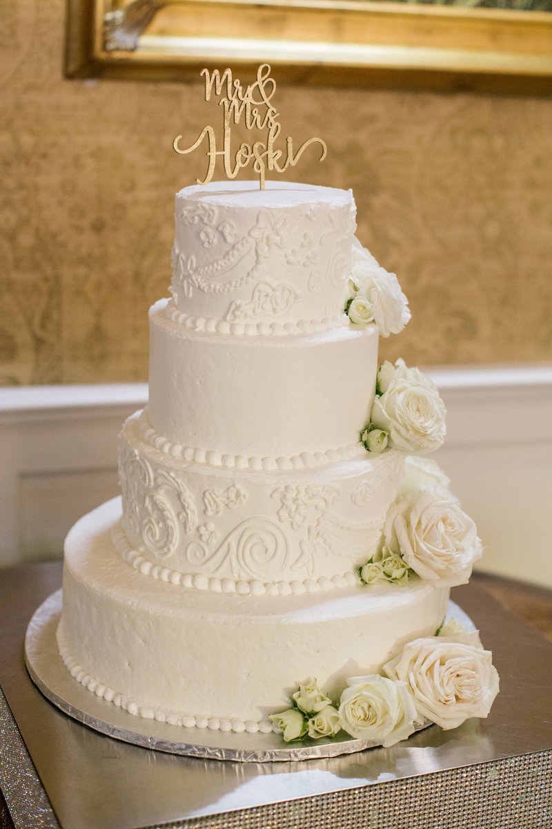 white wedding cake with roses and topper