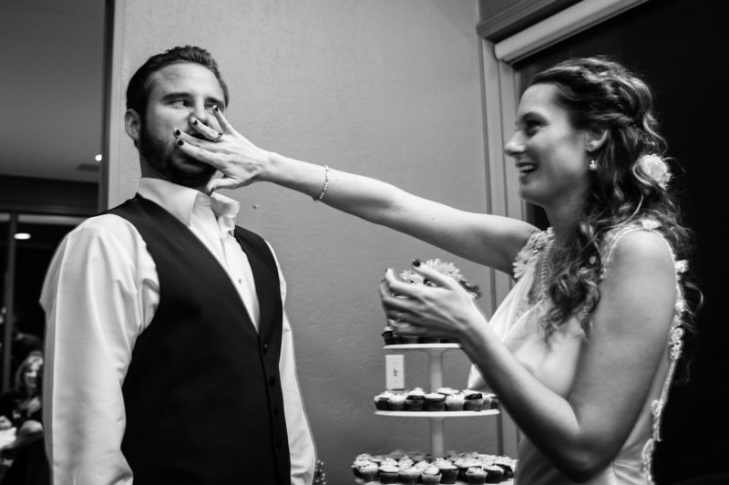 The groom gets a piece of cake smashed into his face during the wedding reception at Eagle Crest Resort. Pete Erickson Photography.