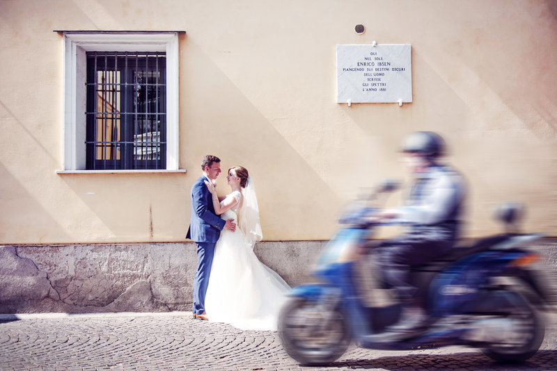 Scooter passes by as bride and groom pose for image in the streets of Sorrento