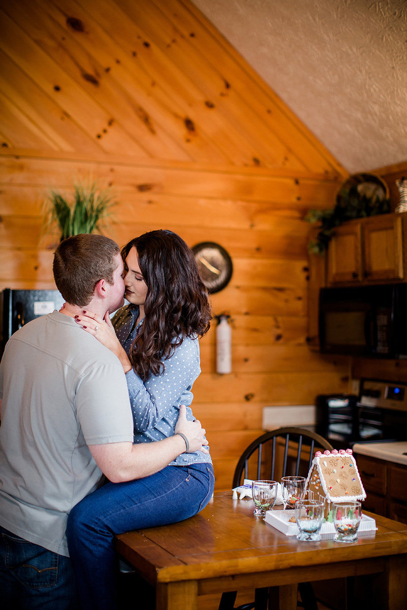 Wife sits on table and kisses her husband in a small cabin in Pigeon Forge by Knoxville Wedding Photographer, Amanda May Photos.