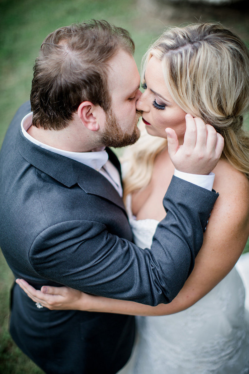 Groom sweeping bride's hair back at Percy Warner Park by Knoxville Wedding Photographer, Amanda May Photos.