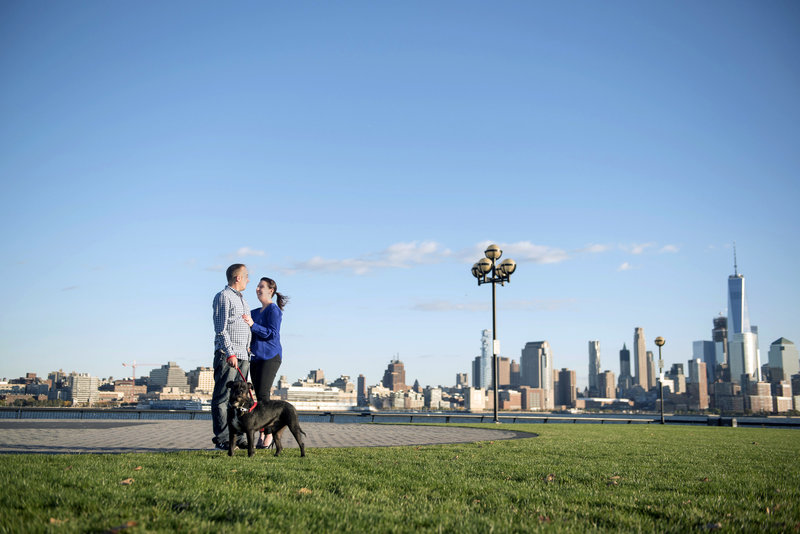 new york skyline from hoboken with couple and their dog