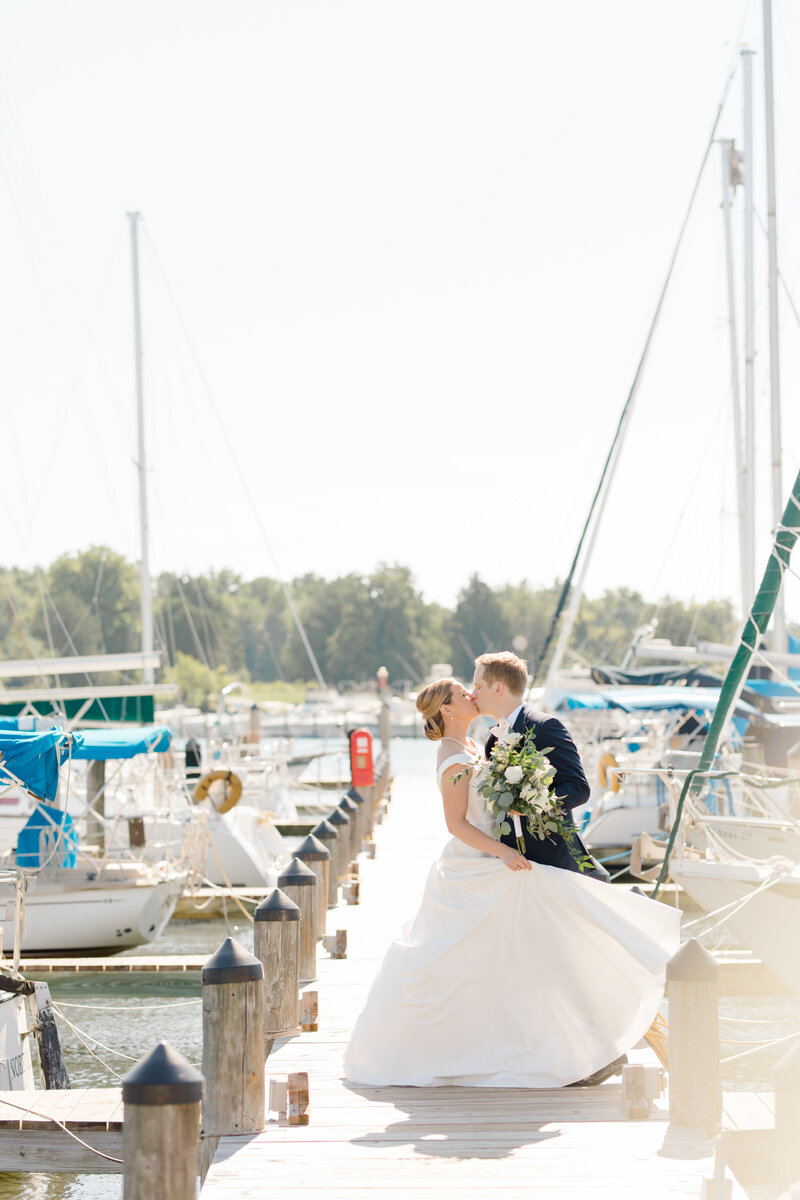bride and groom kissing on pier with sailboats at Inn at Perry Cabin wedding in St Michaels Maryland by Costola Photography