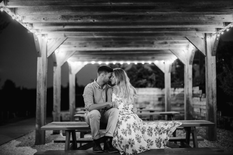 black and white couple sitting on a picnic table outside under awning