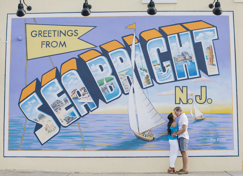 couple kissing in front of sea bright  post card sign