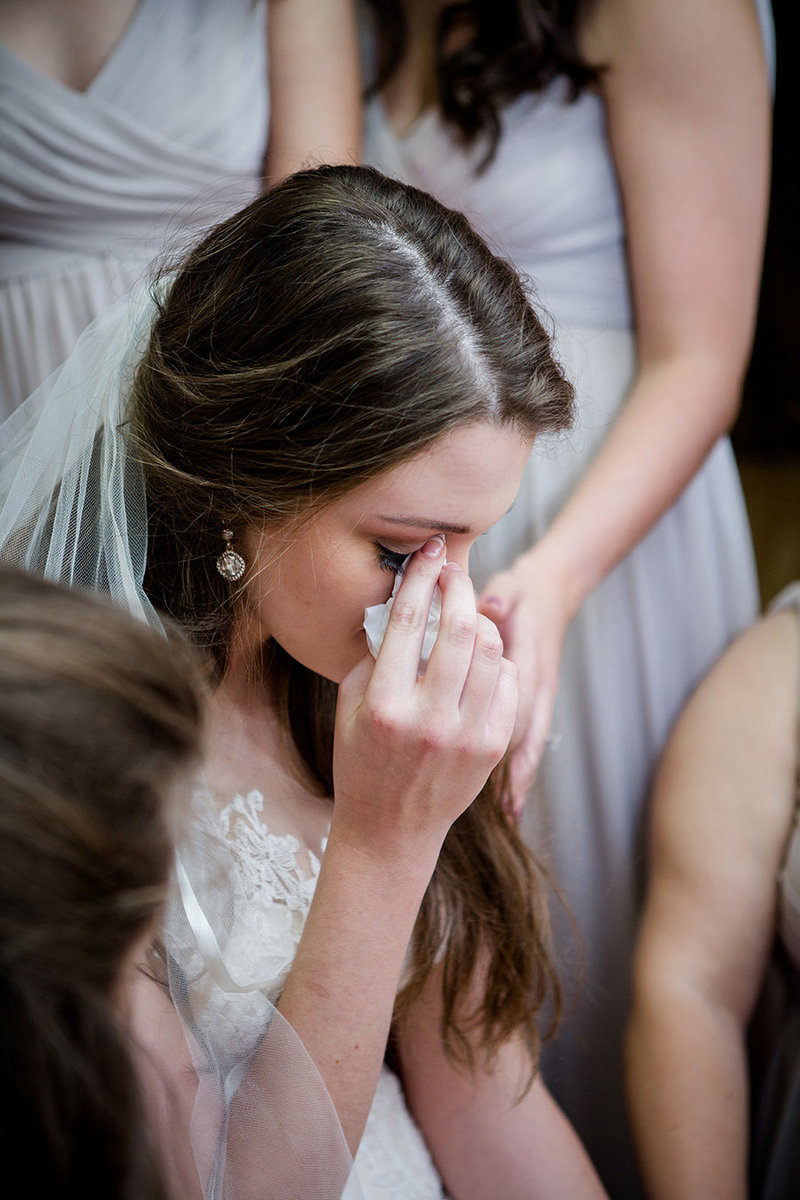 Bride wipes away her tears as her bridesmaids pray for her at her little white chapel wedding by Knoxville Wedding Photographer, Amanda May Photos.
