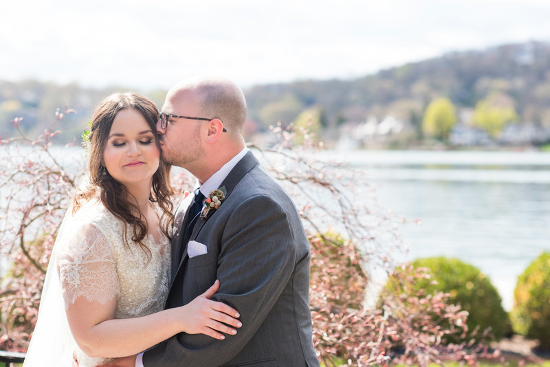 groom kisses bride on the cheep after first look