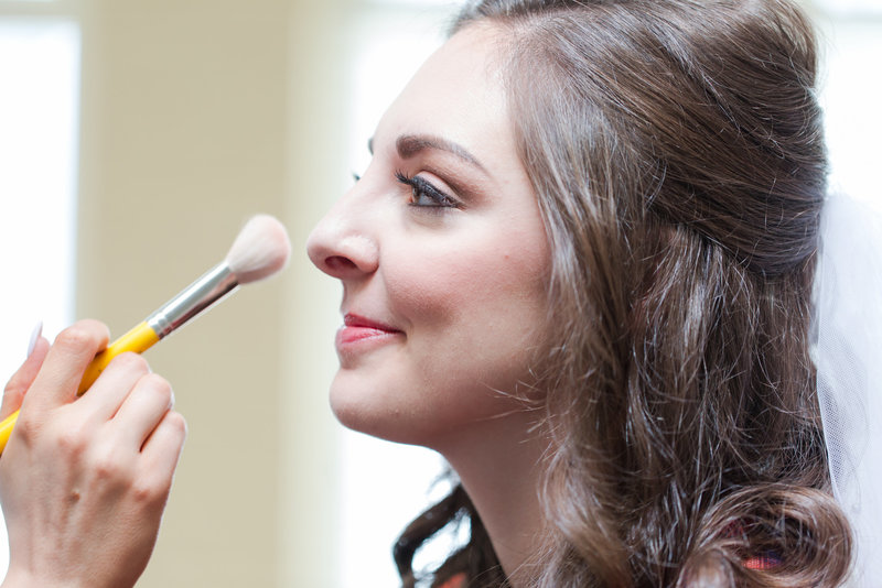 Bride looks at makeup brush as makeup artist does her makeup