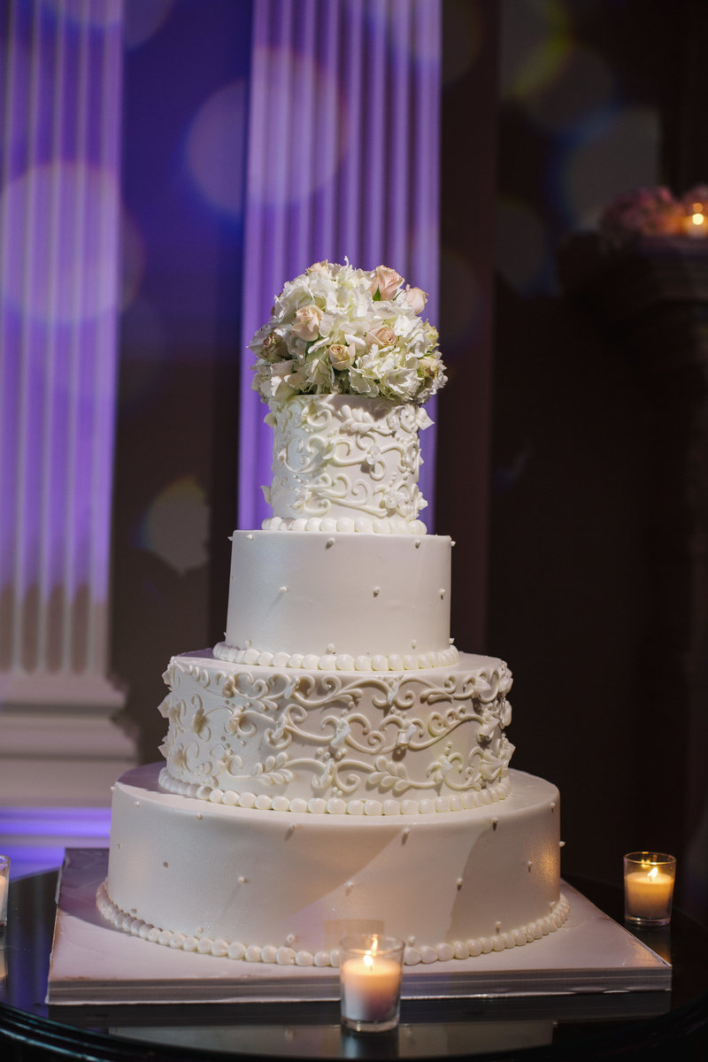 white wedding cake with flower topper at the park savoy